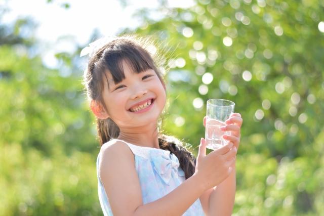 水を飲んで笑顔の子ども